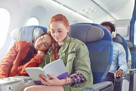 Affectionate young lesbian couple sleeping and reading on airplaneの写真素材 [FYI02179646]