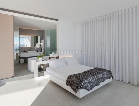 Bed in modern, luxury home showcase interior bedroom with en suite bathroomの写真素材 [FYI02179650]