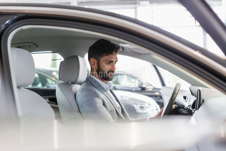 Male customer sitting in driver's seat of new car in car dealership showroomの写真素材 [FYI02179651]