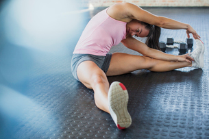 Young woman stretching leg and side in gymの写真素材 [FYI02179656]