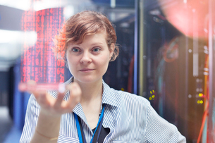 Female IT technician holding futuristic digital tablet in server roomの写真素材 [FYI02179658]