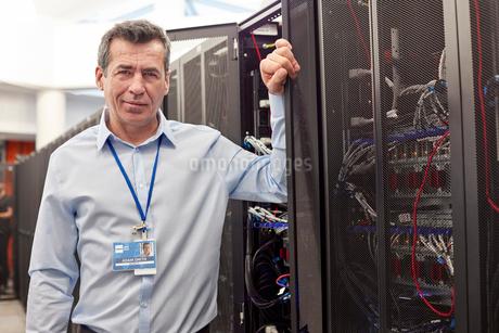 Portrait confident male IT technician in server roomの写真素材 [FYI02179663]