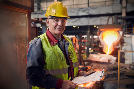 Portrait confident steelworker supervisor with clipboard in steel millの写真素材 [FYI02179713]