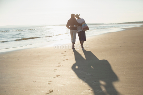 Affectionate mature couple hugging and walking on sunny beachの写真素材 [FYI02179749]