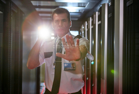 Portrait male security guard with flashlight gesturing stop in server roomの写真素材 [FYI02179786]