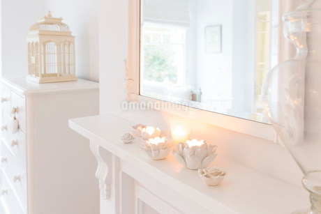Tranquil candles in flower candleholders on white mantleの写真素材 [FYI02179788]