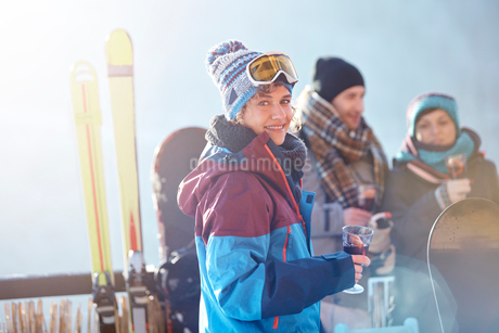 Portrait smiling female skier drinking cocktail on balcony with friends apres-skiの写真素材 [FYI02179795]