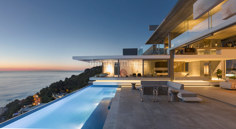 Illuminated modern, luxury home showcase exterior patio with lap pool and ocean view at twilightの写真素材 [FYI02179829]