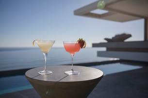 Cocktails in martini glasses on sunny luxury patio with sunny ocean viewの写真素材 [FYI02179860]
