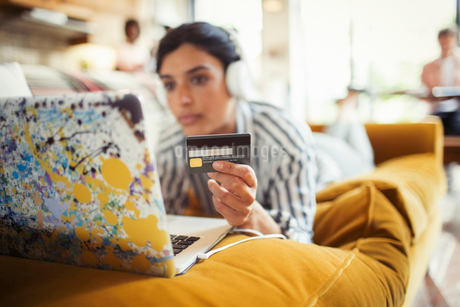 Young woman with headphones and credit card online shopping at laptop on living room sofaの写真素材 [FYI02179933]
