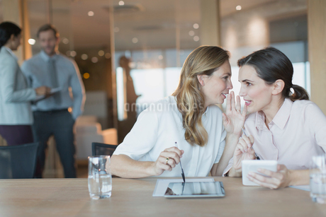 Businesswomen with digital tablets whispering in conference room meetingの写真素材 [FYI02179966]
