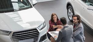Car salesman shaking hands with female customer in car dealership showroomの写真素材 [FYI02179988]