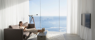 Woman relaxing with feet up, watching TV in modern, luxury home showcase interior living room with sの写真素材 [FYI02180023]