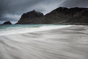 Blurred motion ocean beach tide below rugged mountains, Haukland Beach, Lofoten, Norwayの写真素材 [FYI02180051]