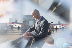 Businessman checking smart watch on urban streetの写真素材 [FYI02180059]