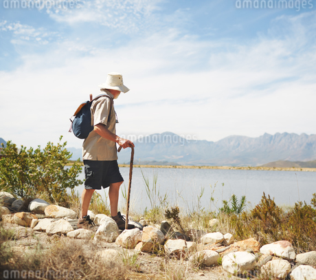 Male hiker with backpack and walking stick at sunny summer lakesideの写真素材 [FYI02180112]