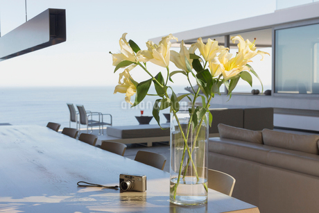 Yellow lily bouquet in vase on modern, luxury home showcase interior dining table next to digital caの写真素材 [FYI02180124]
