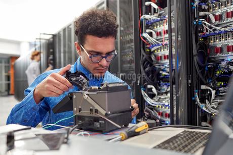 Male IT technician fixing equipment in server roomの写真素材 [FYI02180129]