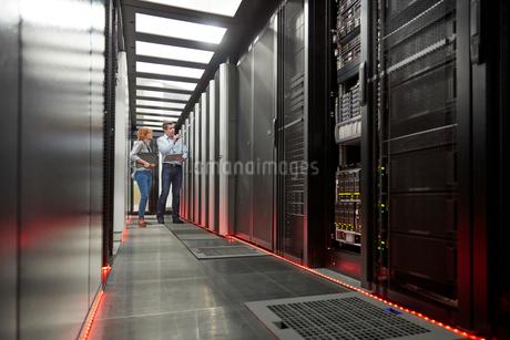 IT technicians talking at panel in server roomの写真素材 [FYI02180156]