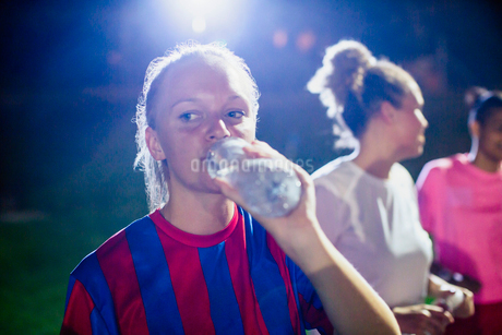Young female soccer player drinking from water bottleの写真素材 [FYI02180202]