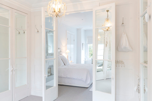 White, luxury home showcase interior bedroom with French doors and chandelierの写真素材 [FYI02180216]