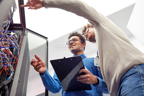 Male IT technicians with clipboard talking at panel in server roomの写真素材 [FYI02180286]