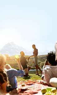 Friends watching young man proposing to woman at sunny summer picnicの写真素材 [FYI02180291]