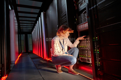 Female IT technician examining panel in dark server roomの写真素材 [FYI02180332]