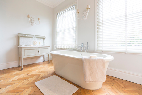 White, luxury home showcase interior bathroom with soaking tub and parquet hardwood floorの写真素材 [FYI02180348]