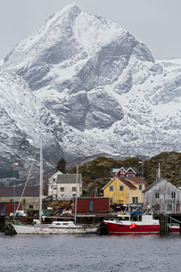 Fishing village and boats at waterfront below snowy, rugged mountains, Sund, Lofoten, Norwayの写真素材 [FYI02180354]