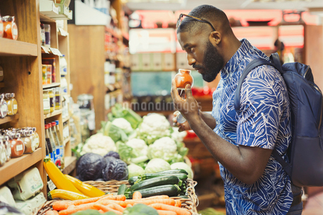 Man shopping, smelling spices in grocery storeの写真素材 [FYI02180356]