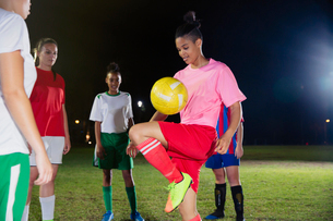Young female soccer player practicing, bouncing ball on knee on field at nightの写真素材 [FYI02180361]