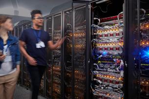 IT technicians walking along panels in server roomの写真素材 [FYI02180396]