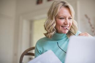 Smiling mature female freelancer working at laptop at homeの写真素材 [FYI02180402]
