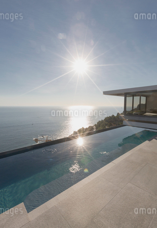 View of sun shining over ocean and modern, luxury home showcase exterior lap pool patioの写真素材 [FYI02180410]