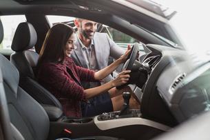 Car salesman and female customer in driver's seat of new car in car dealership showroomの写真素材 [FYI02180422]