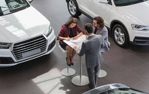 Car salesman watching couple customers signing financial contract paperwork in car dealership showroの写真素材 [FYI02180442]