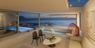Illuminated modern, luxury home showcase living room and pool with twilight ocean viewの写真素材 [FYI02180483]