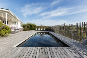 Tranquil home showcase swimming pool surrounded by wooden deckの写真素材 [FYI02180489]