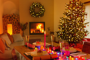 Ambient Christmas dinner table in living room with fireplace and Christmas treeの写真素材 [FYI02180494]