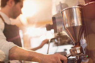 Barista using espresso machine grinder in cafeの写真素材 [FYI02180506]