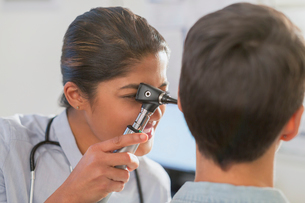 Female doctor using otoscope in ear of patientの写真素材 [FYI02180513]