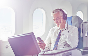 Businessman with headphones watching movie on airplaneの写真素材 [FYI02180547]
