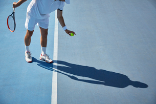 Young male tennis player playing tennis, bouncing tennis ball on sunny blue tennis courtの写真素材 [FYI02180550]