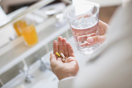 Woman taking vitamins and glass of waterの写真素材 [FYI02180560]