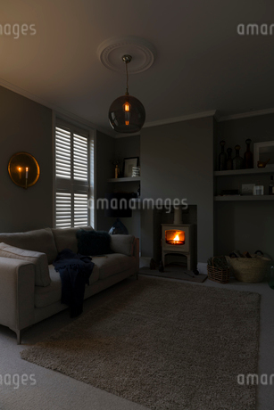 Dim chandelier and wood burning stove in home showcase living roomの写真素材 [FYI02180563]