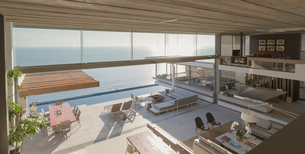 Elevated view modern, luxury home showcase interior living room and patio with sunny ocean viewの写真素材 [FYI02180569]