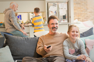 Male gay parents watching TV and bonding with childrenの写真素材 [FYI02180612]