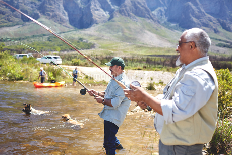 Active senior men friends fishing at sunny summer lakeの写真素材 [FYI02180645]