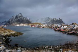Fishing village at waterfront below snowy, rugged mountains, Reine, Lofoten, Norwayの写真素材 [FYI02180768]